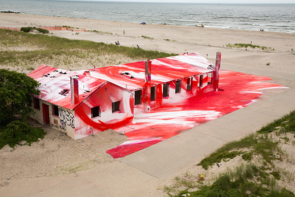 Abandoned building on Fort Tilden beach covered in red and white paint by artist Katharina Grosse