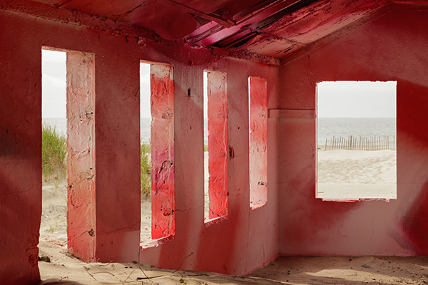 Interior of abandoned building on the beach upcycled with red and white paint by artist Katharina Grosse