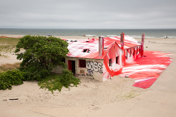 Abandoned building on the beach upcycled with red and white paint by artist Katharina Grosse