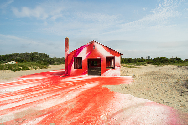 Abandoned building on the beach upcycled with red and white paint