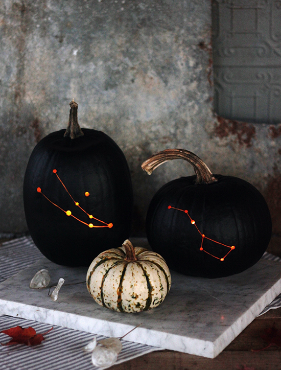 Black pumpkins carved with constellations by The Merrythought