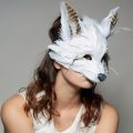 Woman wearing white fox mask made of feathers