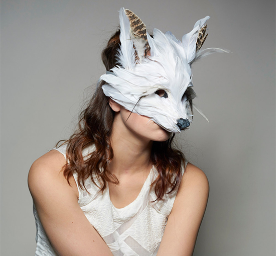 Woman wearing white fox mask made of feathers and vintage fabrics