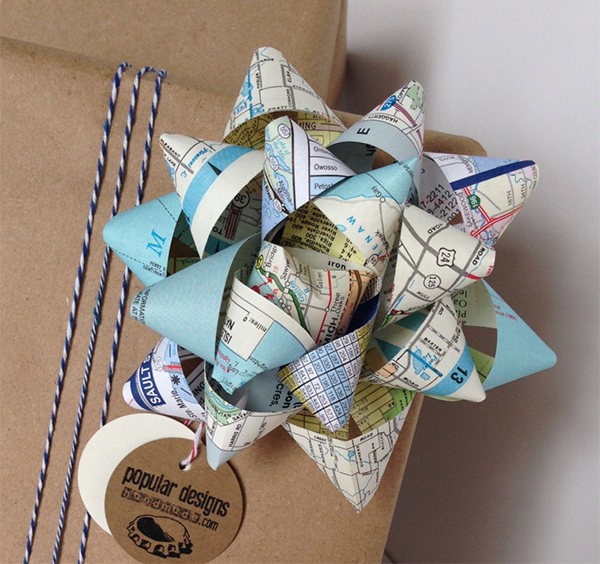 Gift wrapped in brown paper with bow made from recycled maps