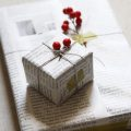 Gifts wrapped in magazine pages with twine and berries