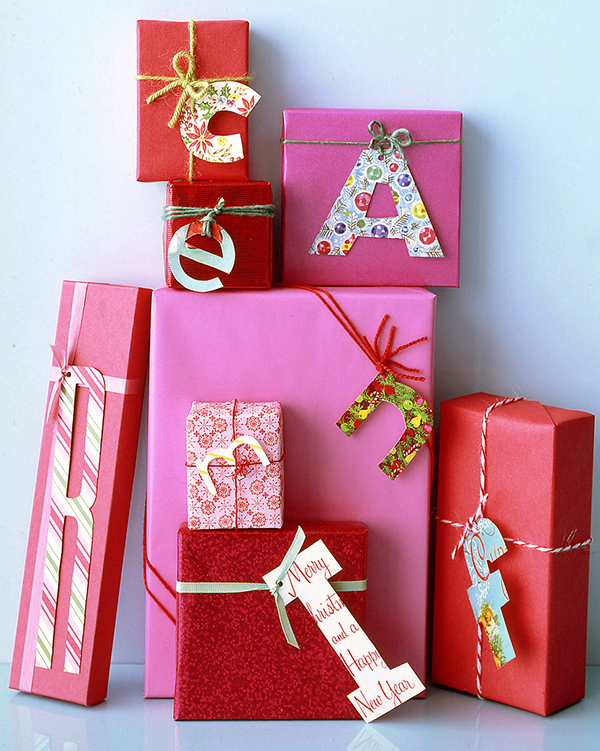 Gifts wrapped in pink and red paper with upcycled christmas card monogram gifts tags