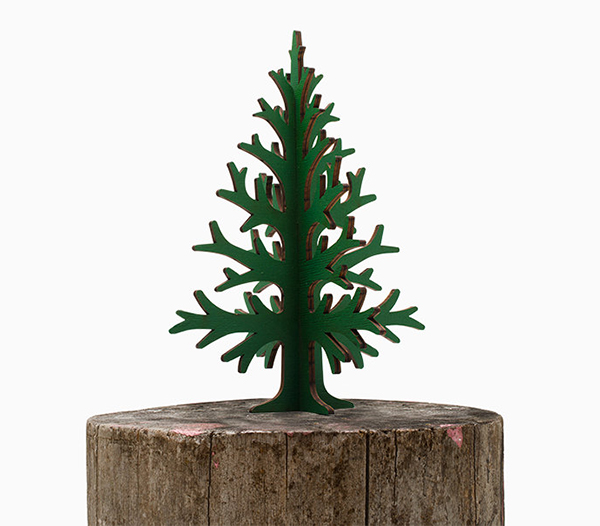 Green christmas tree made of cardboard sitting on a log