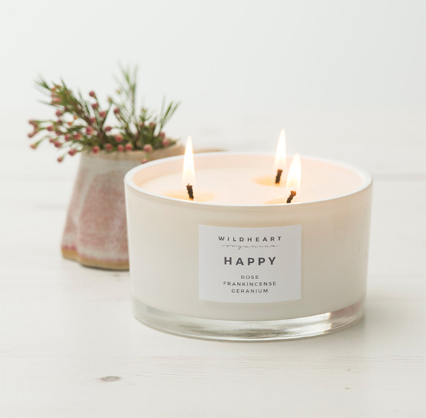 Lit scented candle with 3 flames by Wildheart Organics