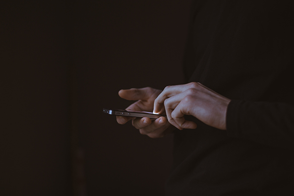 Man dressed in black checking mobile phone