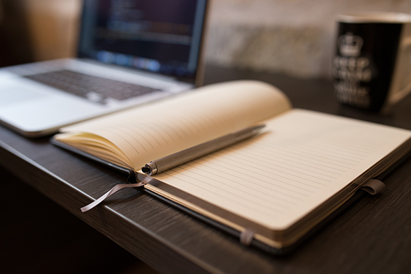 Notebook open at blank page on a desk