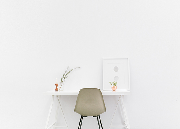 White wall with white desk and grey chair