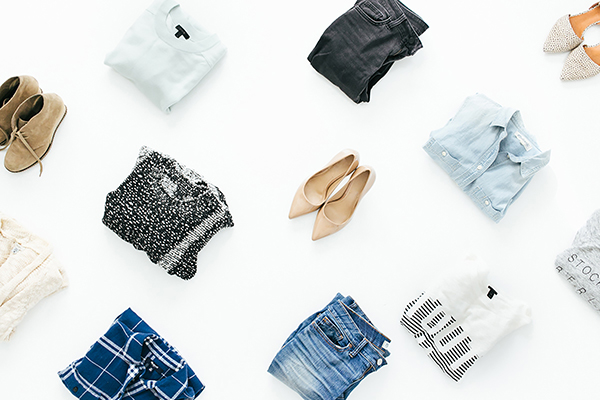 folded clothes and shoes positioned on white floor