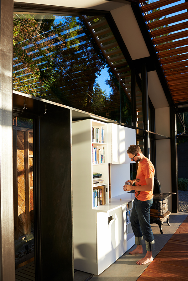man making a drink next to Corian unit in a holiday cabin