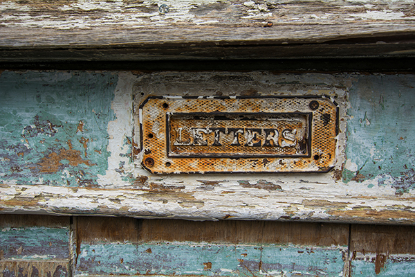 rusty letter box on old blue door