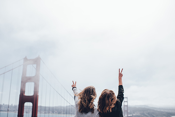 two women giving peace sign next to a bridge