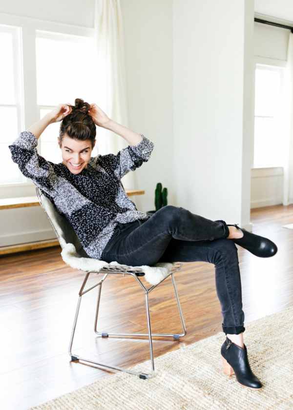 woman sitting on a chair wearing jeans and jumper