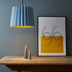 Blue paper lampshade by Lane with grey wall behind