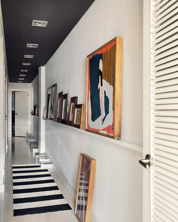 Long narrow corridor with black ceiling and pictures displayed on shallow shelf