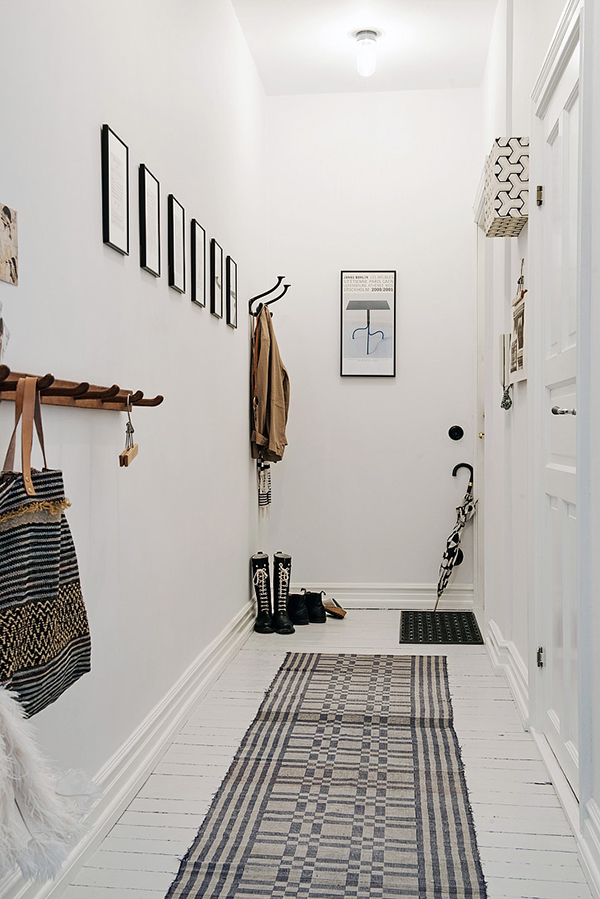 Narrow corridor painted white with white floors and monochrome details