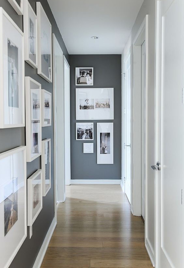 Narrow corridor with dark painted walls and pictures in white frames