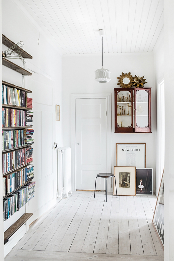 Stylish hallway painted white with book shelves
