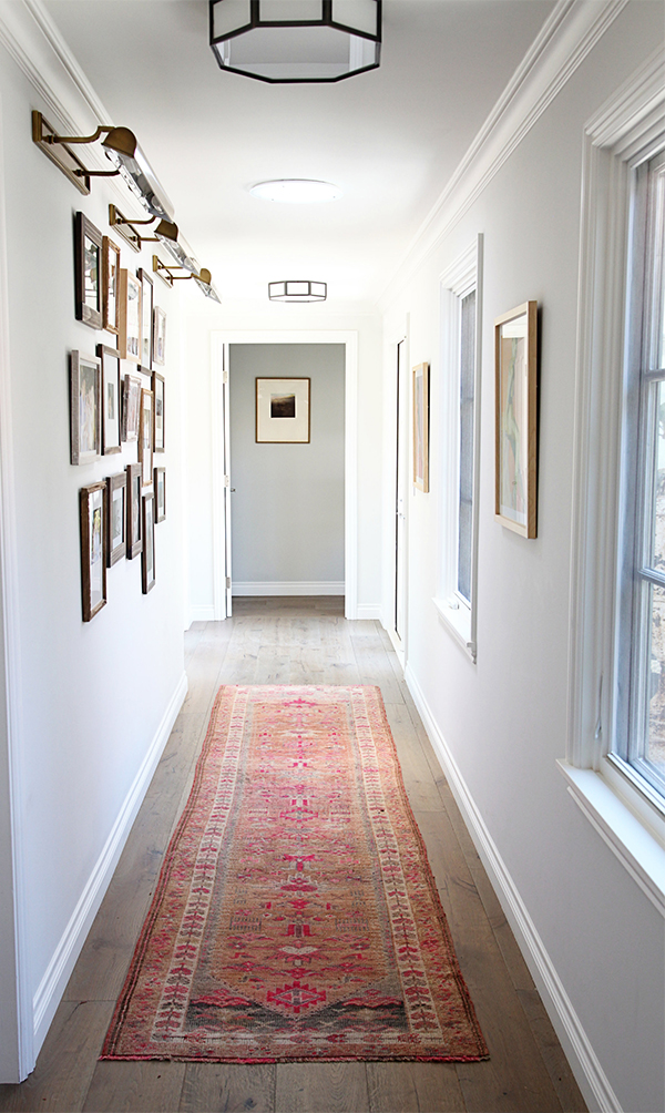 White painted narrow corridor with red rug and photo gallery