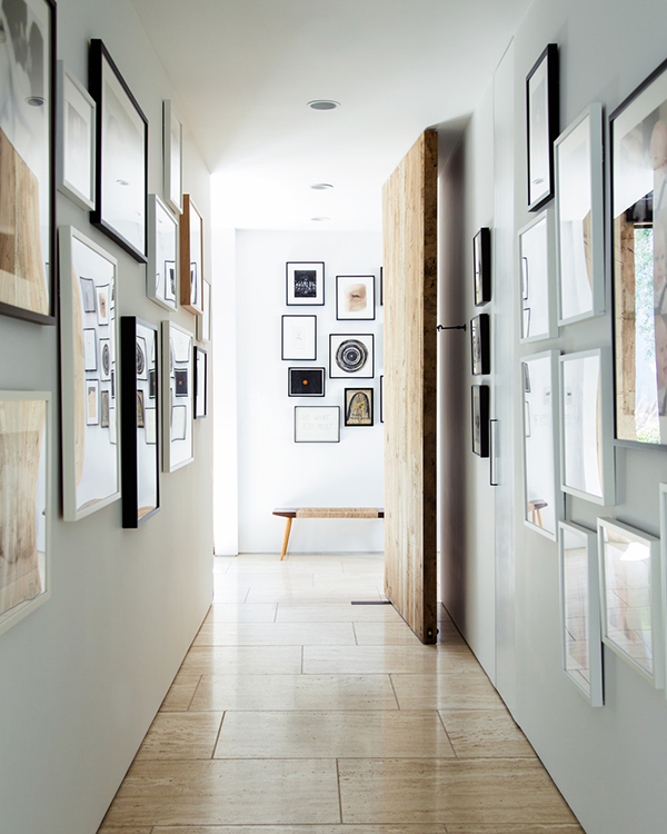 dark corridor with light flooring and framed pictures