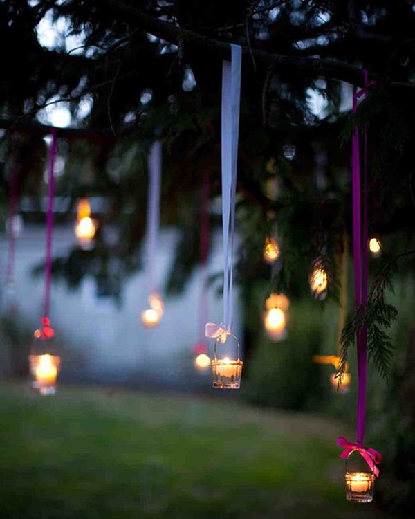 lanterns hanging on trees with ribbon