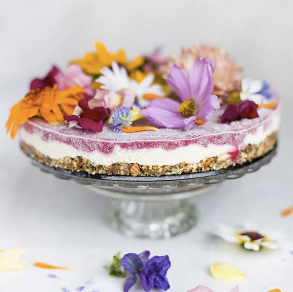 Cake topped with edible flowers by Green Kitchen Stories