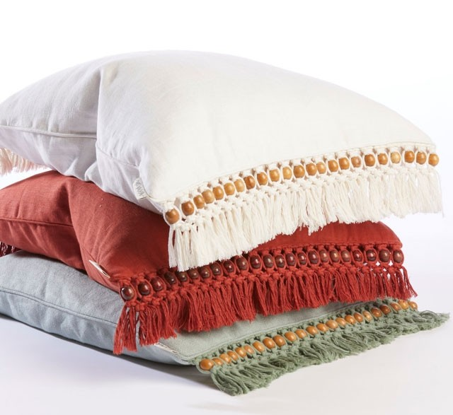Pile of fringed beaded cushions made from recycled cotton