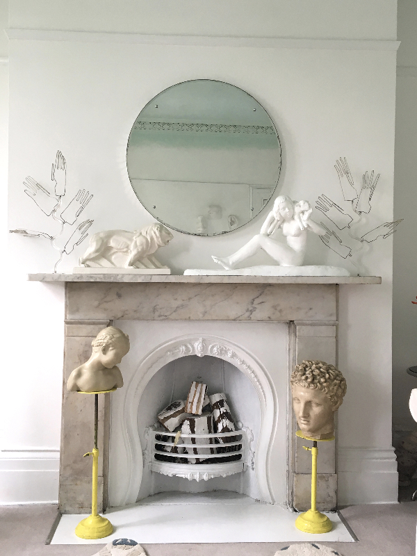 Art and sculpture displayed on a marble fireplace
