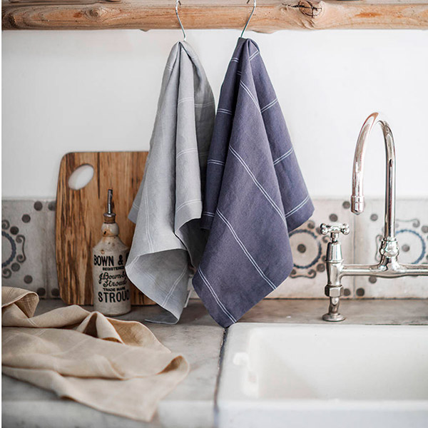 Grey Italian stripe linen tea towels hanging above the sink in a modern rustic kitchen