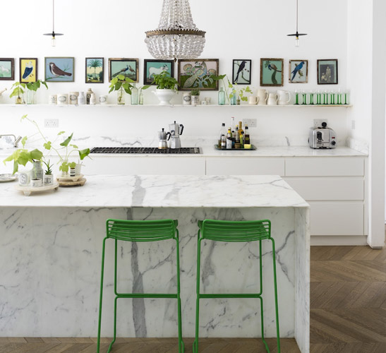 Modern kitchen with marble island and green accents