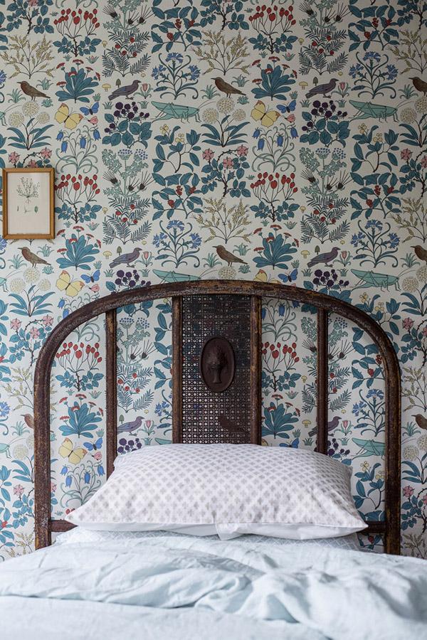 vintage bed frame with patterned wallpaper behind