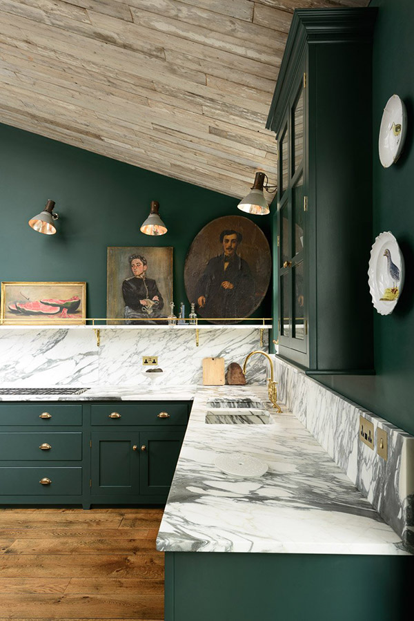 Dark green painted kitchen with marble worktops and art display