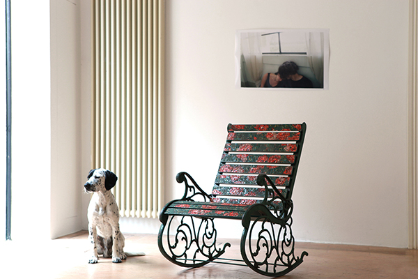 Dog sitting next to a reworked rocking chair by Yukiko Nagai