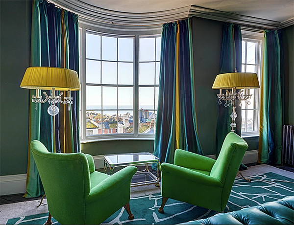 Green upholstered armchairs in blue and green interior by Hossack and Gray