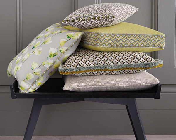 Pile of yellow and grey bespoke cushions by Fineline Upholstery London