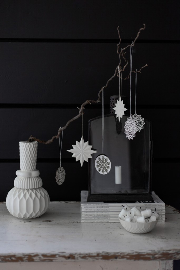 Branch decoration in white vase with black wall behind