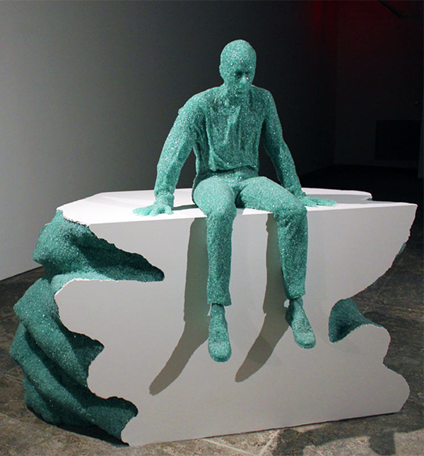Seated man made of shattered glass by Daniel Arsham