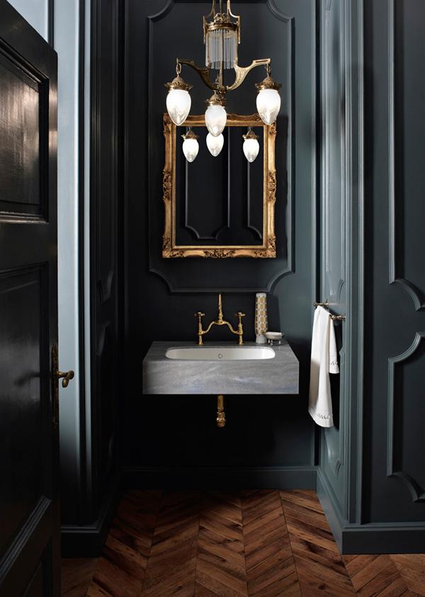 Dark walls in the bathroom with vintage mirror and modern corian sink