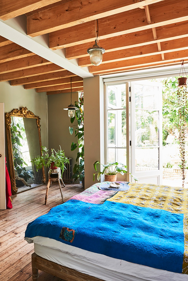 Exposed beams with wooden floors and plants in the bedroom