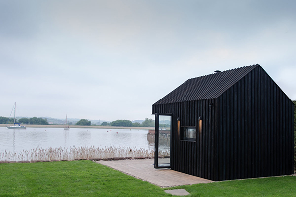 Black contemporary wood cabin on the water