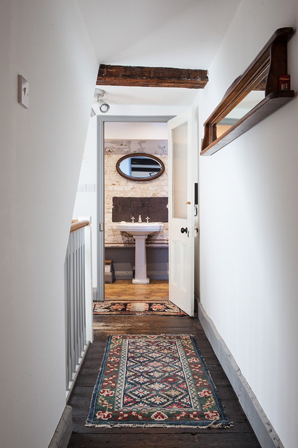 Corridor furnished with vintage rug and reclaimed finds