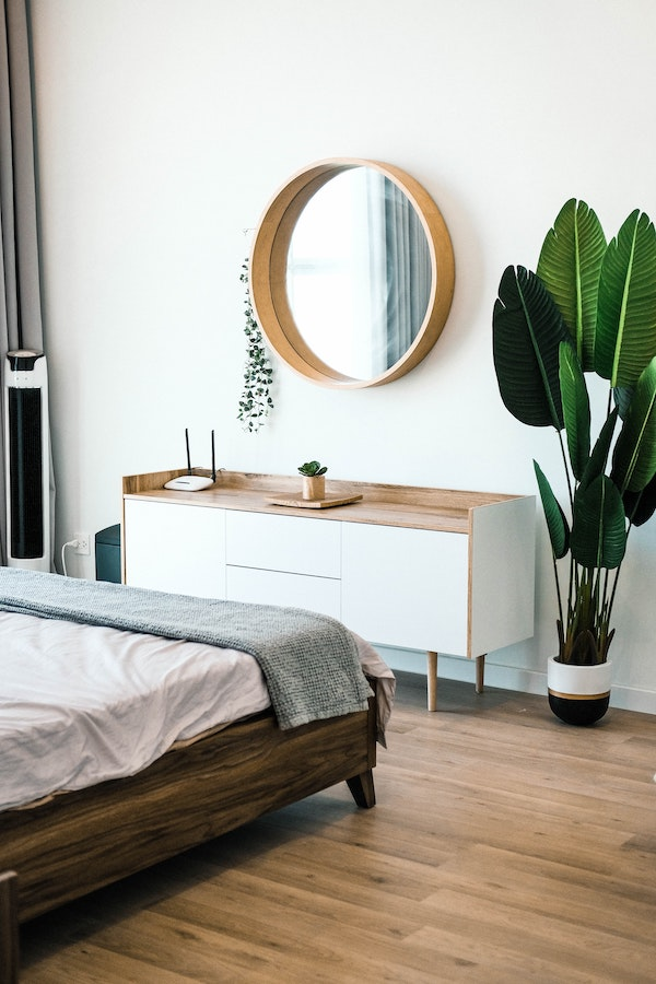 Plants in the bedroom with round mirror